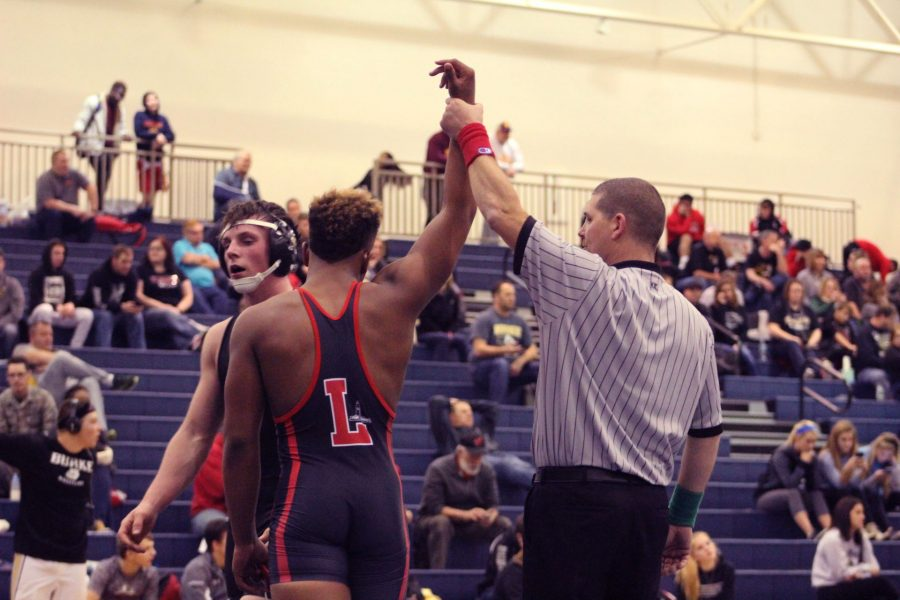 Isaiah Alford raises his hand after winning a match during a tournament at Bellevue East High School on December 10th, 2017.  Photo provided by Isaiah Alford.