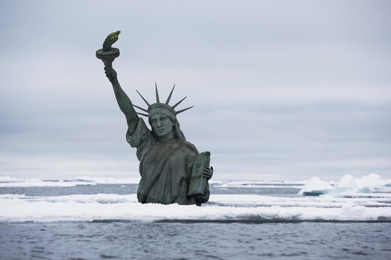A+semi+submerged+Statue+of+Liberty+in+the+Arctic+Ocean+draws+attention+to+the+effects+of+climate+change+on+rising+sea+levels%2C+as+world+leaders+are+about+to+gather+in+New+York+for+the+Climate+Summit+hosted+by+UN+Secretary-General+Ban+Ki-moon.+The+melting+of+Arctic+glaciers+and+ice+sheets+contributes+directly+to+global+sea+level+rise.+The+photo+was+taken+in+the+Arctic+Ocean+northwest+of+Svalbard+the+7th+of+September+2014.