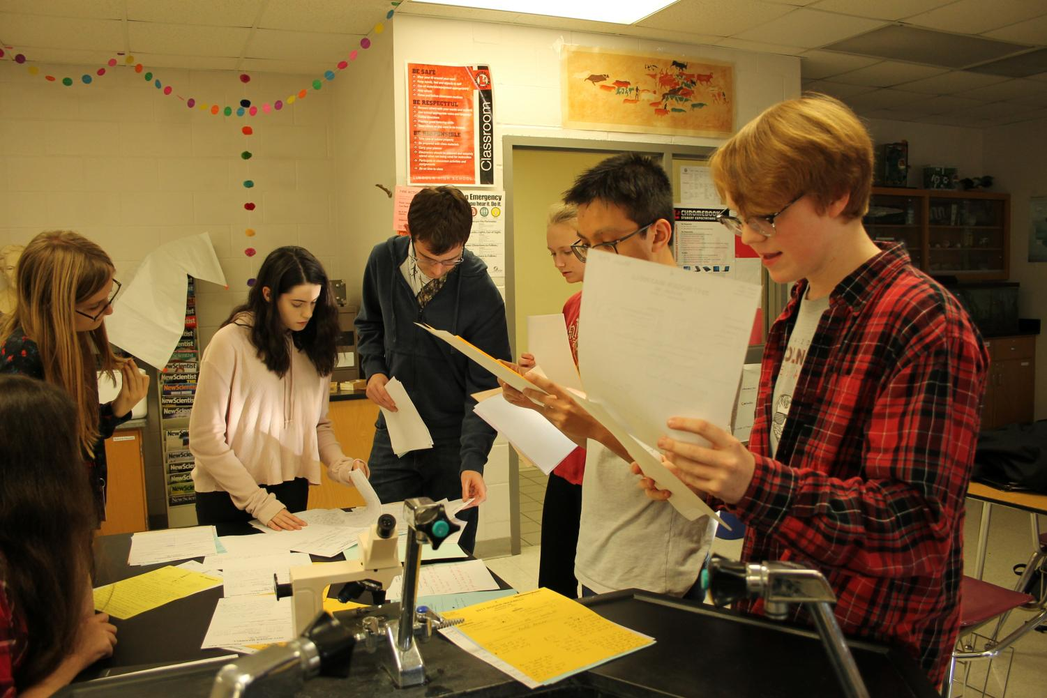The LHS Debate team reviews and shares updated scores from the previous competition at Southwest High School and prepares for upcoming competition in Elkhorn, NE on Saturday November 18, 2017. From left to right: Esmee Krohn (10), Madeleine Walker (10), Janna Marley (9), Keith Tran (12), Rory Helweg (12). Photo by Audrey Perry