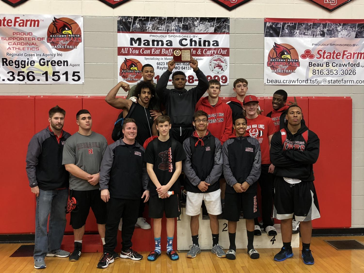 The Links Varsity Wrestling team lines up for a photo as they raise up their 3rd place trophy on December 17, 2017. Photo courtesy of Camden Trevarrow.