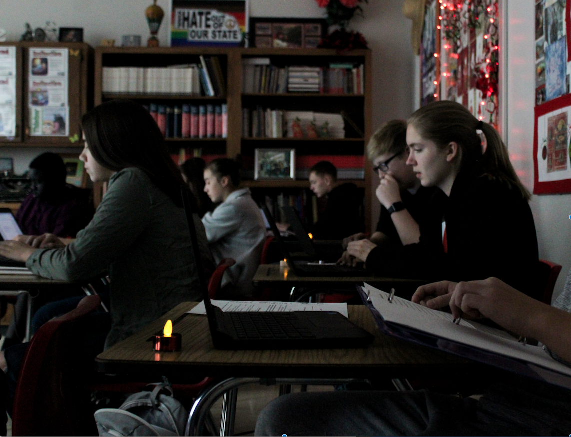 Lydia Skold (left), Jack Amen (right back ) and Olivia Haller (right front) write by candlelight in Deborah McGinn's 9th grade Pre-IB English class. Photo by Maicee Ingwerson