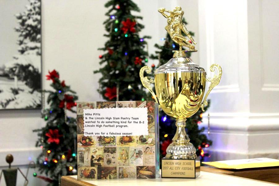 Slam Poets gift trophy to varsity football team