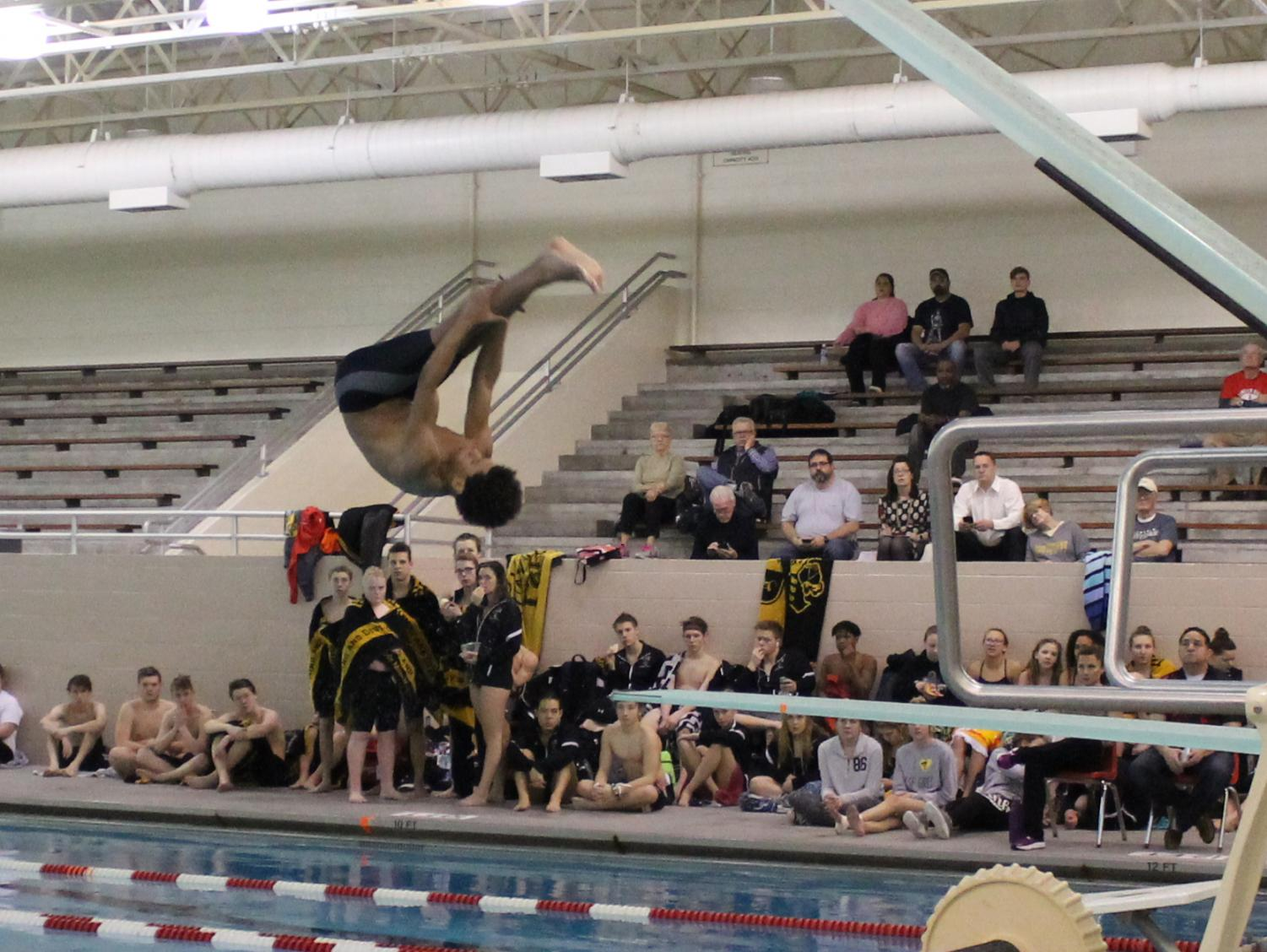 Isaiah Winston (10) does a forward double pike for his second dive at a triangular meet held at Lincoln High on January 25th, 2018 against Fremont and Southeast. Winston scored 320 points at this meet and qualified (again) for state. Photo by Madeline Walker.