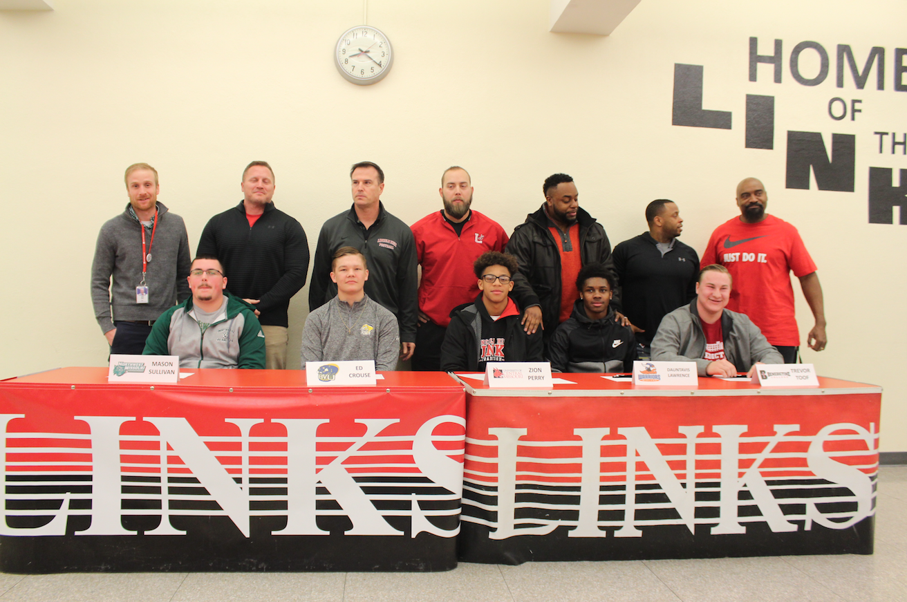 Student-Athletes from Lincoln High School sign to play football at the next level on February 7, 2018. Left to Right: Mason Sullivan, Ed Crouse, Zion Perry, Dontavious Lawrence, and Trevor Toof. The coaches behind the players include Coach Jared Shaw, Coach Chad Case, Coach Mark Macke, Coach Dan Beckmann, Coach John Goodwin, Coach James Watson and Coach Stewart Venable. Photo by Hannah Burianek.