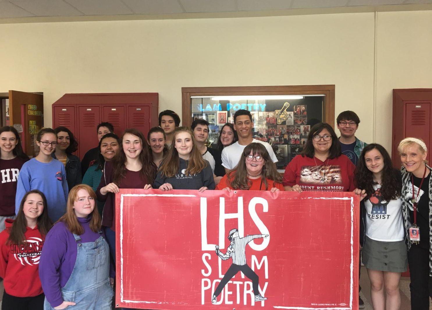 The 2018 LHS Slam Poetry Team poses with their new banner in preparation for their state bout which will be on Tuesday, April 24, 2018 at the Louder Than A Bomb Team Finals at the Holland Center, Omaha - 1200 Douglas St. beginning at 7 p.m.  Photo courtesy of Deborah McGinn