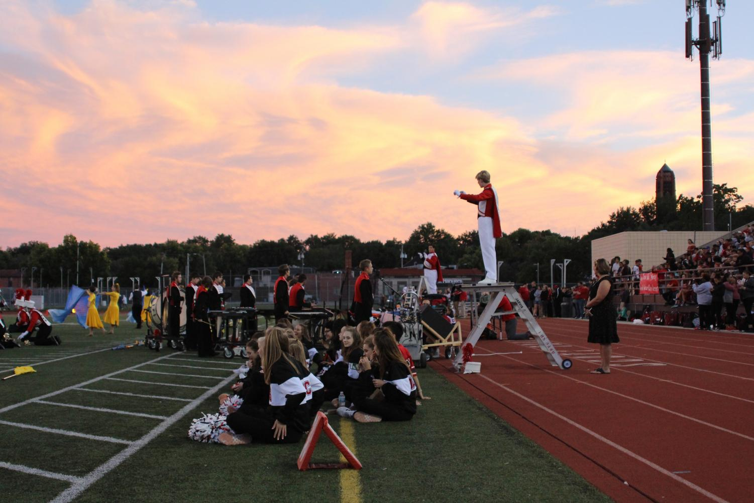 The sky provides a dramatic backdrop as Drum Major Luke Moberly (11) leads the LHS Marching Band in a song at the Homecoming football game on Friday, Sept. 21, 2018 at Beechner Athletic Complex. Saxophone player Jacob Vanderford (11) sings a solo during the performance. The Links defeated Omaha Central 49-6. Photo by Anthony Torres