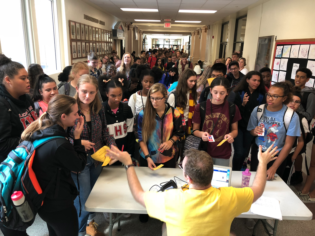 Student Council sponsor Carter Hulinsky tries in vain to get students to form a single line as they pack the main office hallway after school on Wednesday, Sept. 19, 2018 in a last-minute rush to get Homecoming tickets at the $5 price. The line extended almost all the way to the Counseling Center. Tickets went up to $10 on Thursday and will not be sold on Friday. This year's theme is Friday Night Fever.