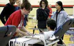 Nebraska Community Blood Bank Nurse Holly Feese helps Bryant Pedreza (12) donate blood during the Red Cross Club Blood Drive in the West Gym on Friday, Oct. 5, 2018 while Will Brandt (12), Passmore Mudundulu (12), Zane Morales (10), and Cecelia Nguyen (10) provide moral support. Photo by Meg Boedeker