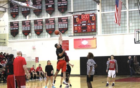 Faculty members start the 2018 Hoops for Hope game with a jump. Students officiated and coached the teams. Photo by Dat Nguyen.