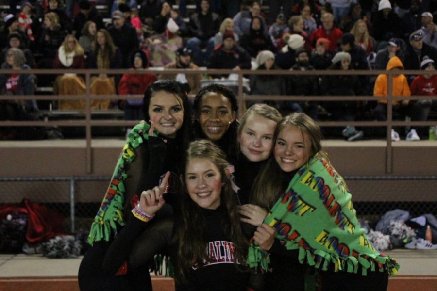 (From Left to Right) Pomalinks Maddie Behrens (11), Zainab Funnah (9),  Bridget Wilson (10), Bailey Hanson (10) and Regan Schneider (11) try to stay warm before performing their halftime show for the varsity football game at Lincoln High on October 12th against the Kearney Bearcats. The Links won 66-31. Lows Friday night reached 38 degrees Fahrenheit. Photo by Zeke Williams