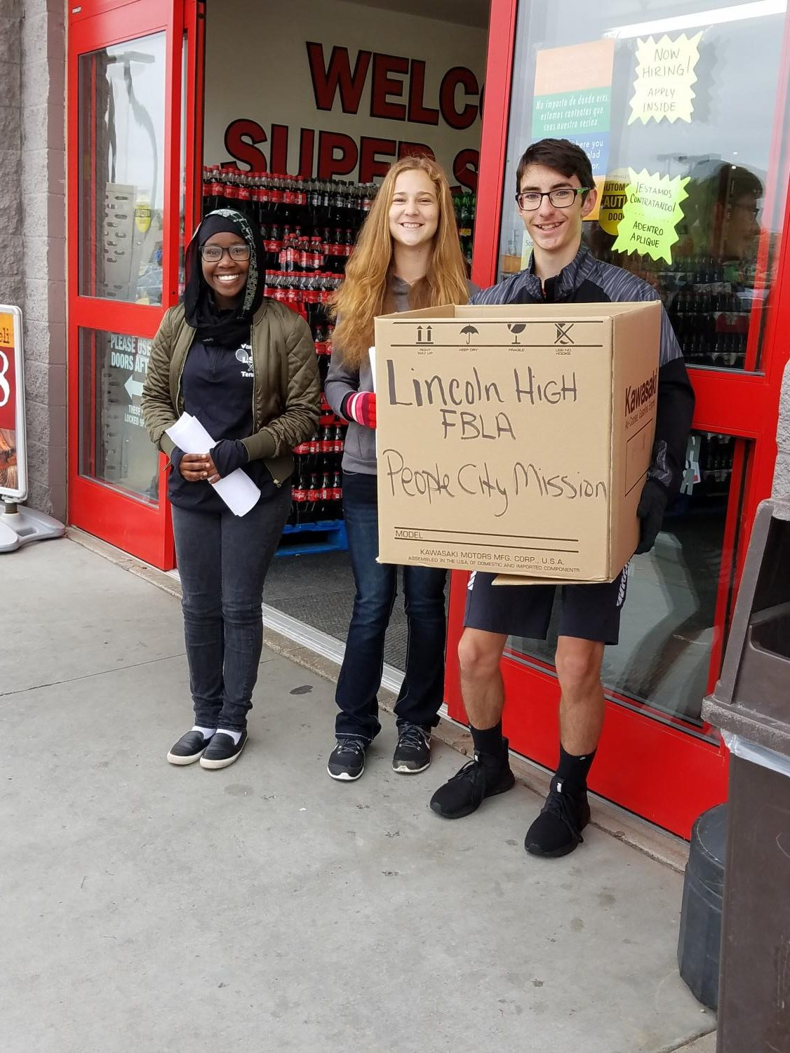 (Left to Right) Meissa Hassan (10), Aspen Kenley (9), and Ethan Fleming (9) pose with the boxes of food they collected at the 27th and Cornhusker Super Saver for the FBLA Food Blitz fundraiser for the Lincoln People's City Mission on Oct. 6, 2018. Photo courtesy of Bonnie Anderson