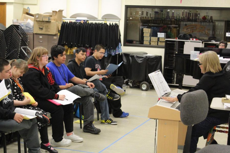 Choir Director Katherine Huerta Simpson leads the Vocal Links Choir in song during their daily rehearsal. The choir is currently working on their winter concert music, which includes songs from