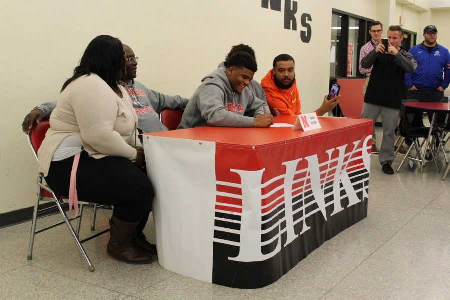 Isaiah Alford (12), on the 27th of November, smiles while signing his wrestling scholarship.