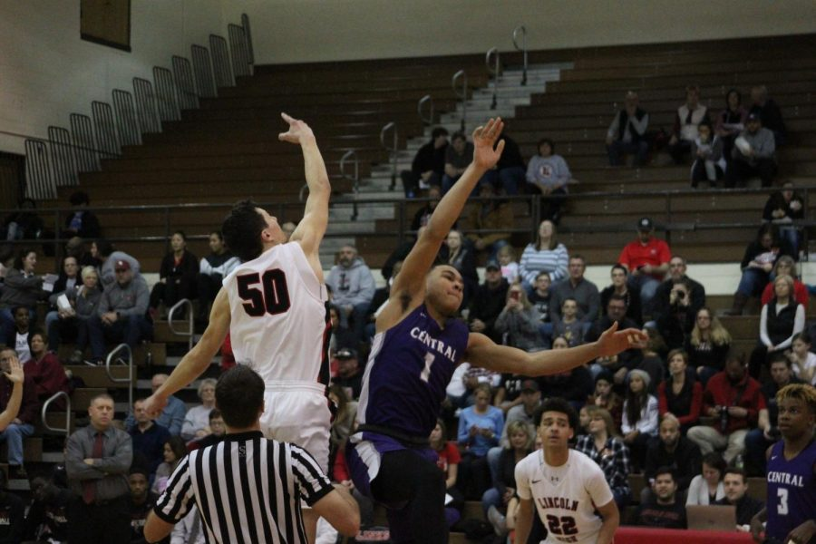 Senior #50 Graham Newton jumps up at tip off against Omaha Central High School on Saturday, January 12th, 2019.  Photo by Zeke Williams