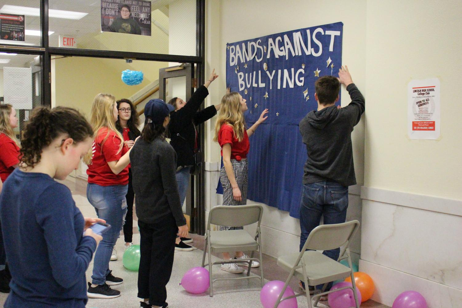 Members of StuCo 2017-18 hang a poster to set up for Bands Against Bullying. Photo by Nate Kettler.