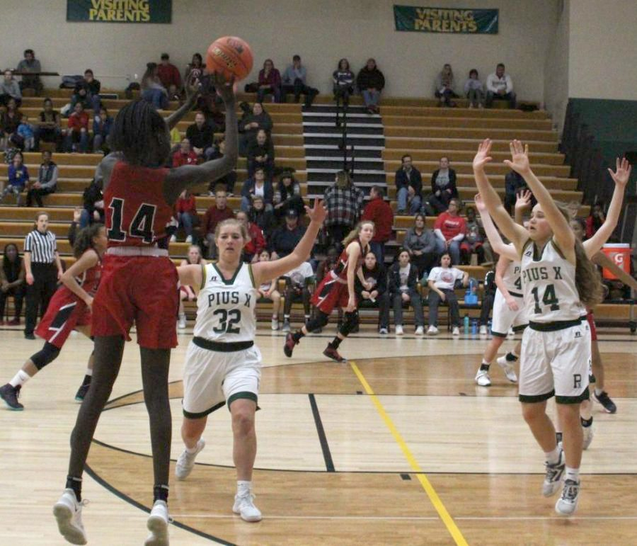 Junior Nyayongah Gony attempts to make a three point shot at Pius X on January 11th, 2019. The Links lost 67-12. Photo by Zeke Williams