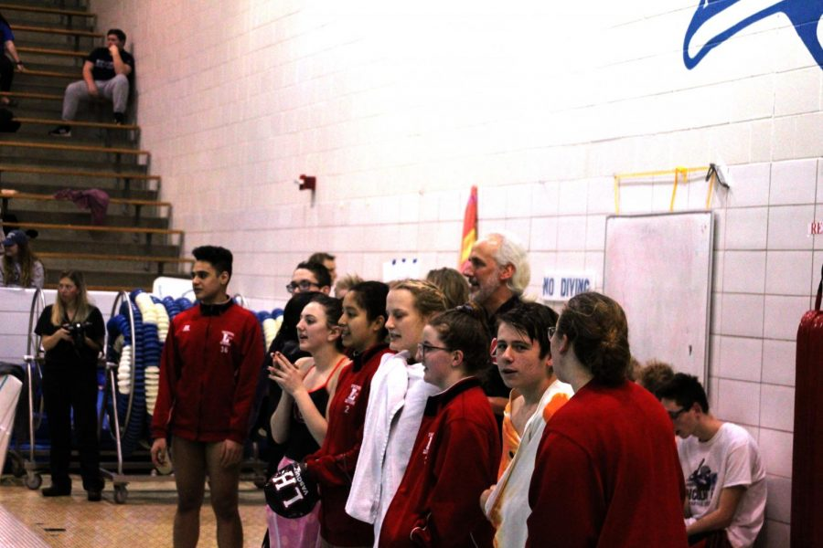 Coach Conrad and other LHS Swimmers cheer on their teammates on January 15th, 2019, at Lincoln East High School. The Links had x new personal records. Photo by Zeke Williams