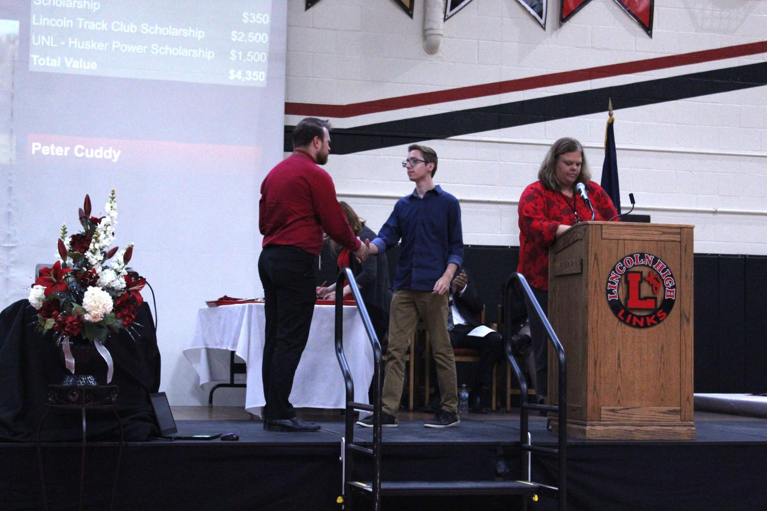 Student Council President Eric Lesiak (12) accepts an award from Music Department Chair Brett Noser at the Senior Honors Assembly on May 13th, 2019. Photo by Linh Ngo