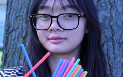 Mai (10) poses with straws and says no to disposable plastic on May 16, 2019. Photo by Audrey Perry.