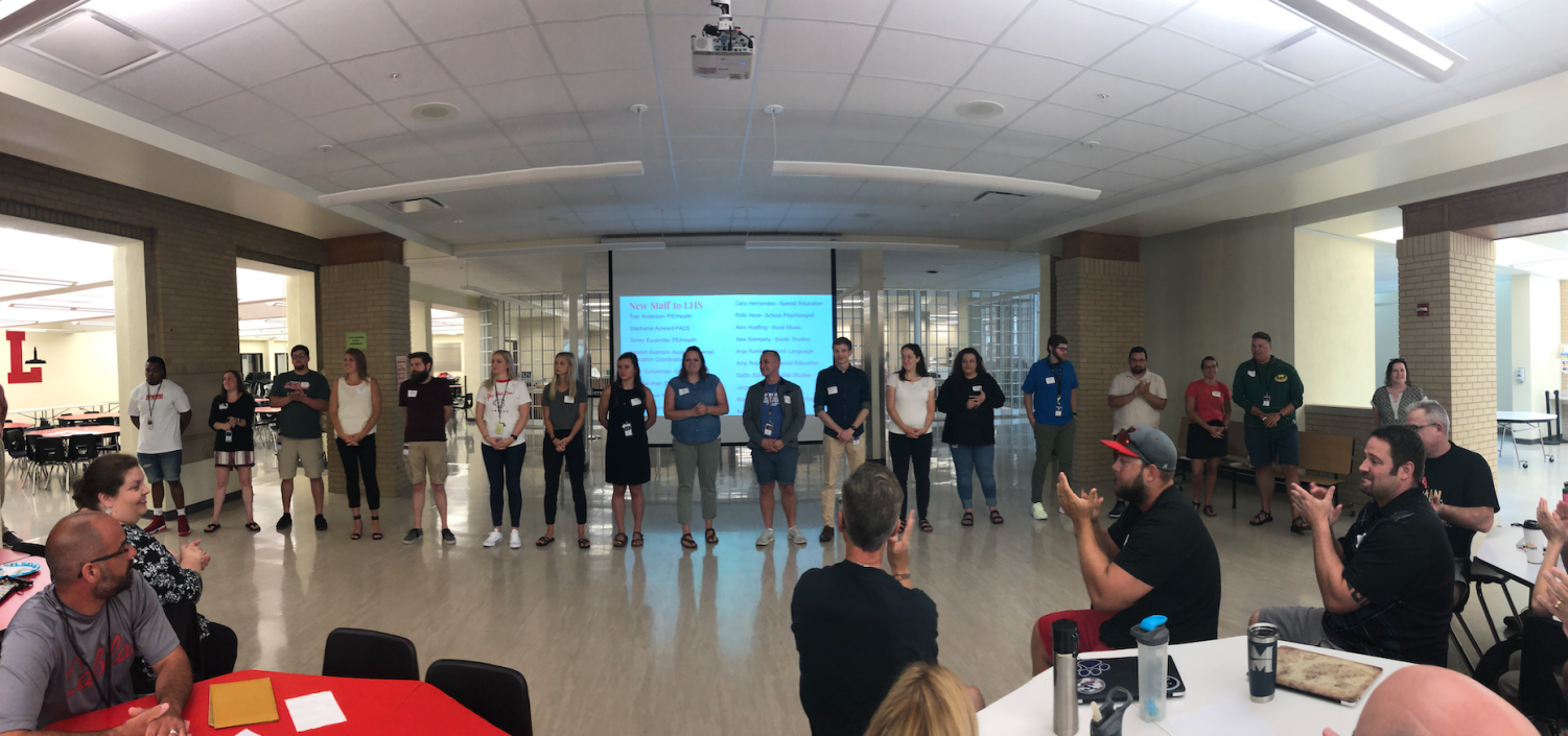 New staff members for the 2020 school year stand to be introduced by Principal Mark Larson at a staff meeting on August 5, 2019.  Lincoln High welcomed 18 new staff members this year.